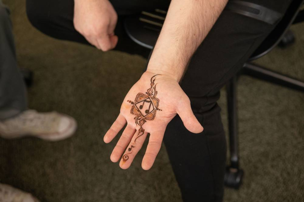 Extended hand showing a henna tattoo with clef sign painted on palm.